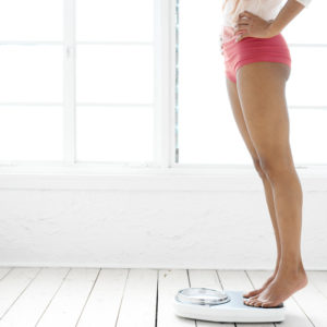 Side profile of the legs of a woman standing on a weighing scale